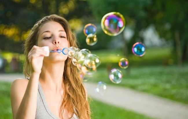 Девушка пускает мыльные пузыри